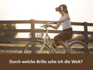 """Foto eines Mädchens auf einem Fahrad mit einer VR-Brille mit dem Text """"Durch welche Brille sehe ich die Welt?"""""""